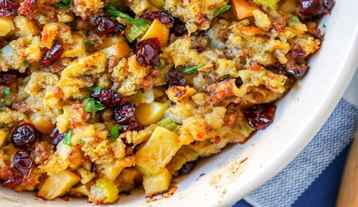 A casserole dish with stuffing made of bread, cranberries and apples.
