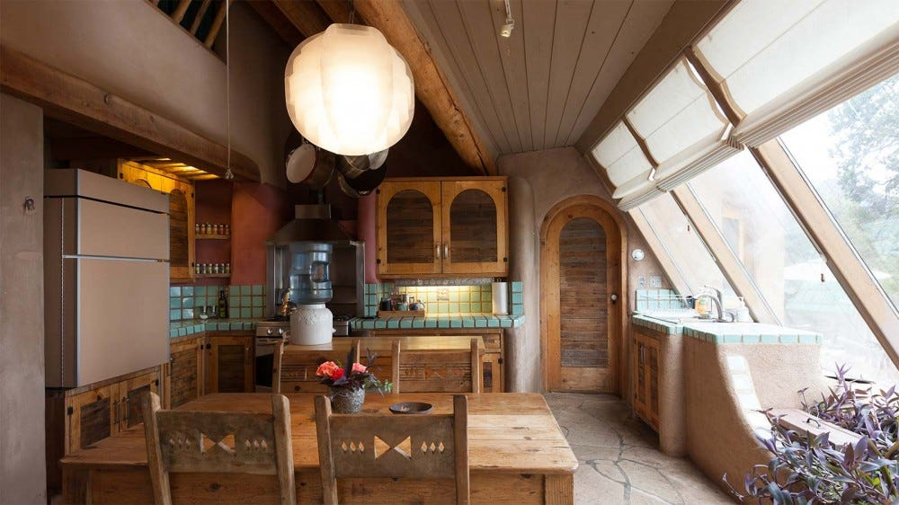 The interior of an Earthship home, showing the organic designs, large windows, and extensive use of stucco.
