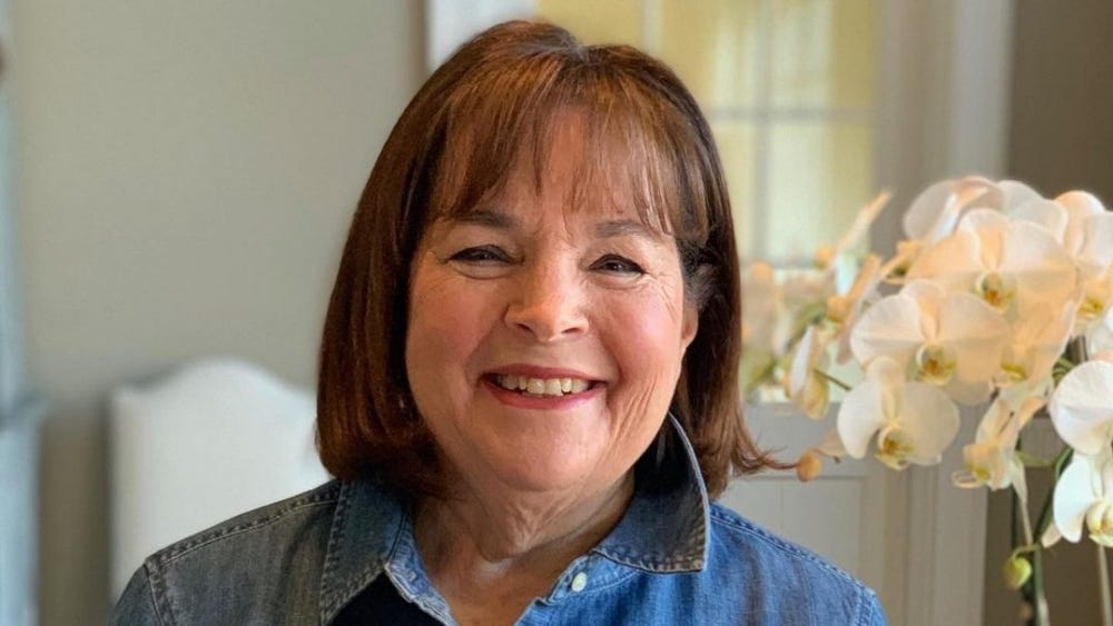 Ina Garten holds her new cookbook and smiles at the camera.