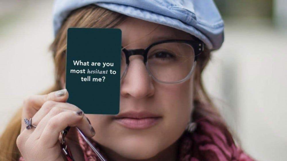Woman holding a Love Language conversation card.