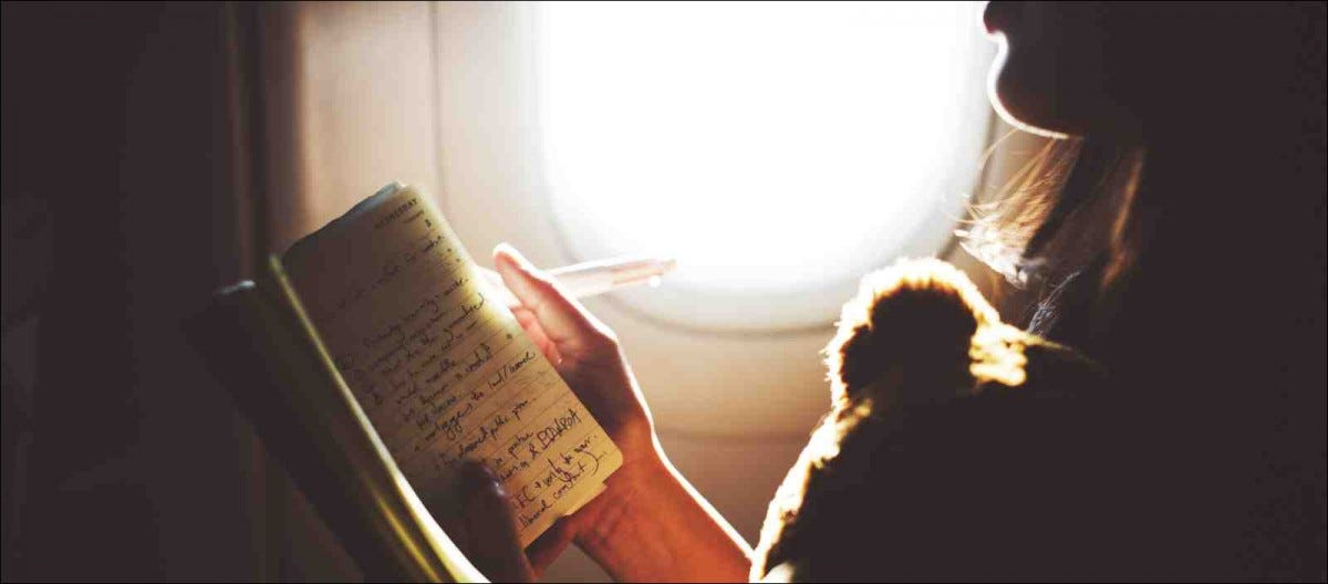 woman writing in journal on plane