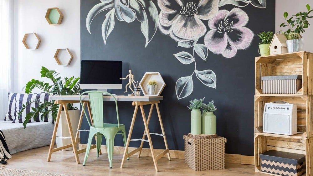 A stylish, modern desk with a large monitor sitting on it, surrounded by wicker and wooden decor.