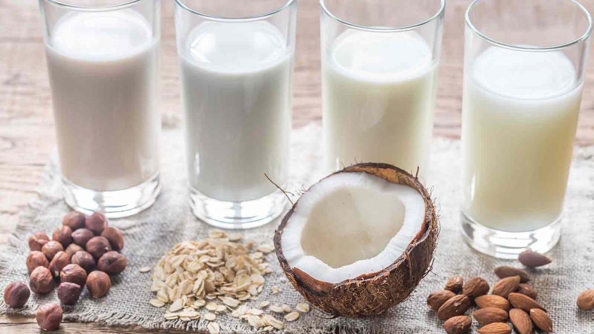 "Four glasses of ""milk"" with a coconut, and piles of almonds and other nuts in front of each."