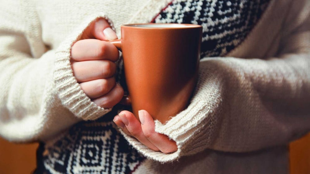 A woman holding a mug filled with a warm soothing drink.