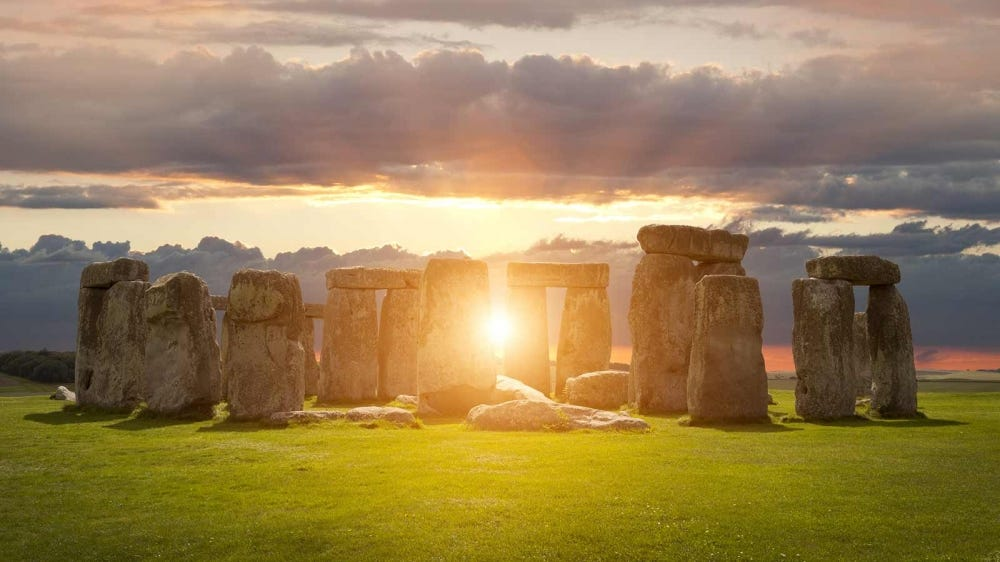 The sun rising through the stones of Stonehenge.