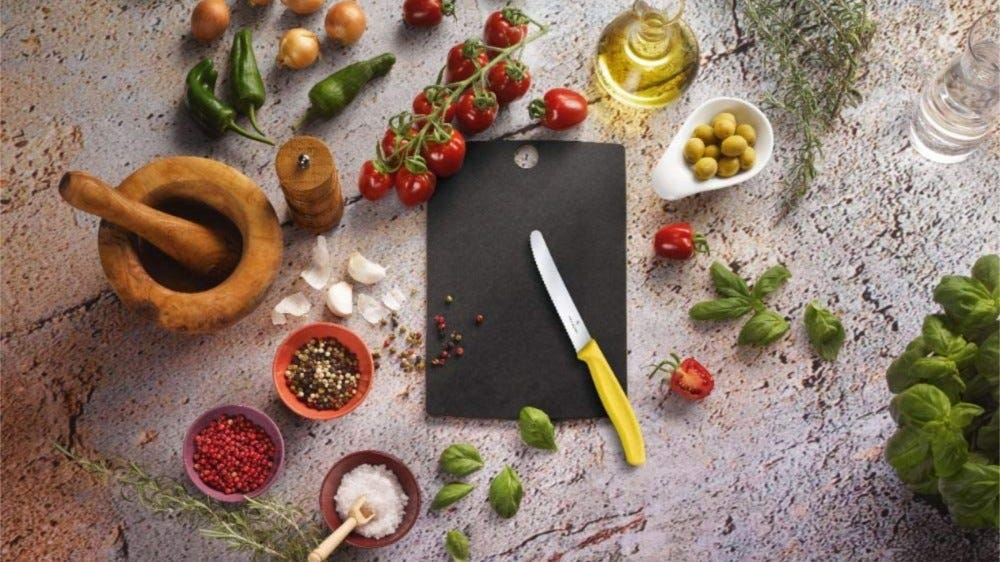 A small black cutting board with a serrated Victorinox blade with different aromatic ingredients around the blade and the board.