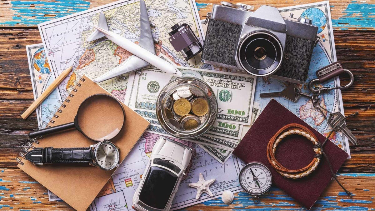A passport, magnifying glass, toy plane, toy car, camera, film, watch, compass, and jar full of change sitting on pile of maps.