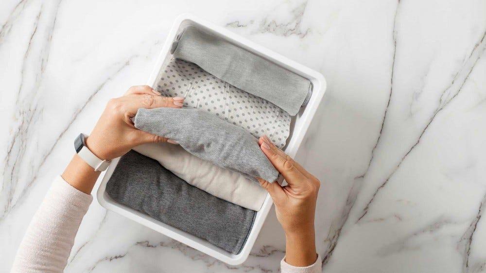 Egy nő szépen összehajtogatja a ruhákat egy fiókszervezőbe.
