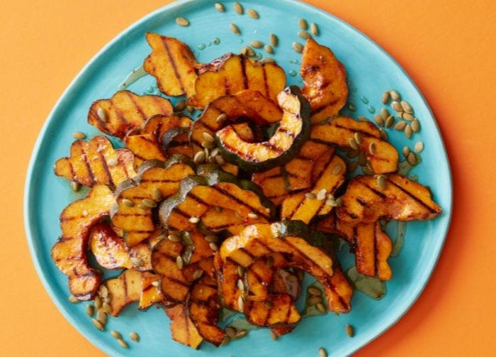 Slices of grilled acorn squash sprinkled with pepitas on a blue plate