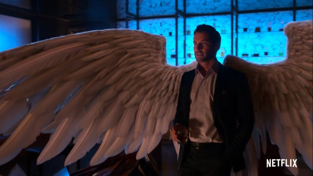 The titular character of Lucifer stands with wings behind his back.