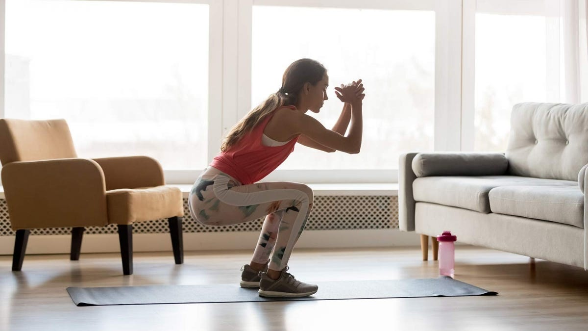 A woman doing a squat on a yoga mat in a living room.