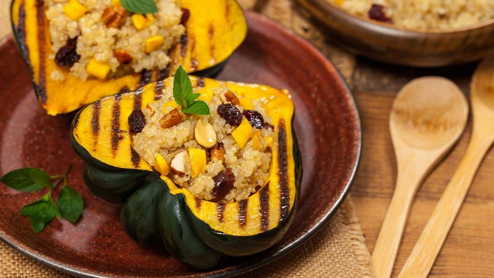 Roasted acorn squash, stuffed with quinoa, nuts, and dried fruit on a plate.