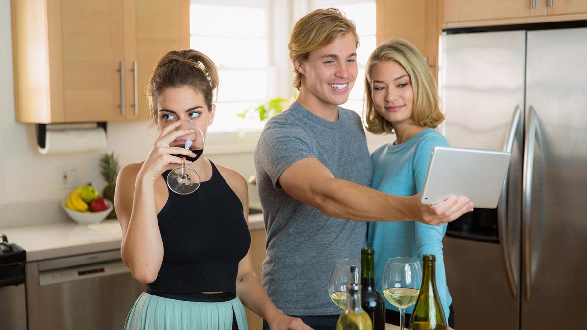 A woman drinking wine and rolling her eyes in a kitchen with a man and woman taking a selfie behind her.