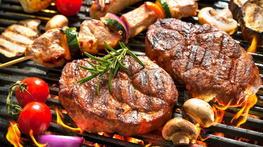 Two steaks, mushrooms, cherry tomatoes, and shish kabob cooking on a grill.
