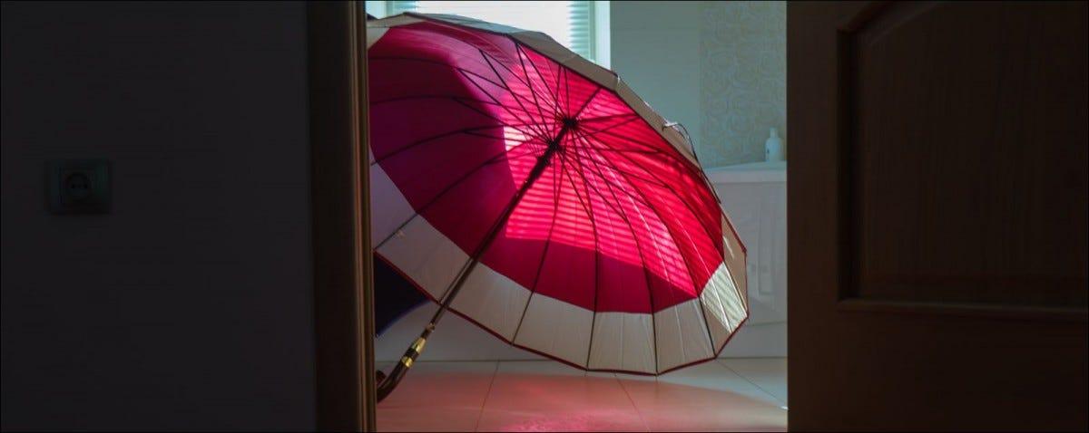 two-color outdoor umbrella open on the bathroom floor