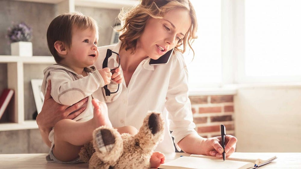 A mom holding a baby while writing in a day planner.