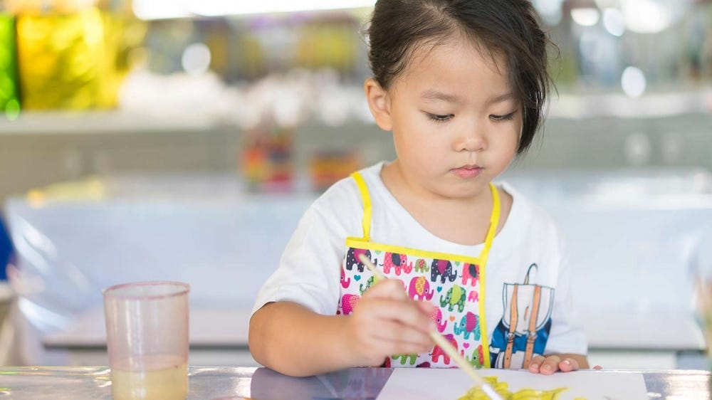 A little girl sitting at a table painting with watercolors.