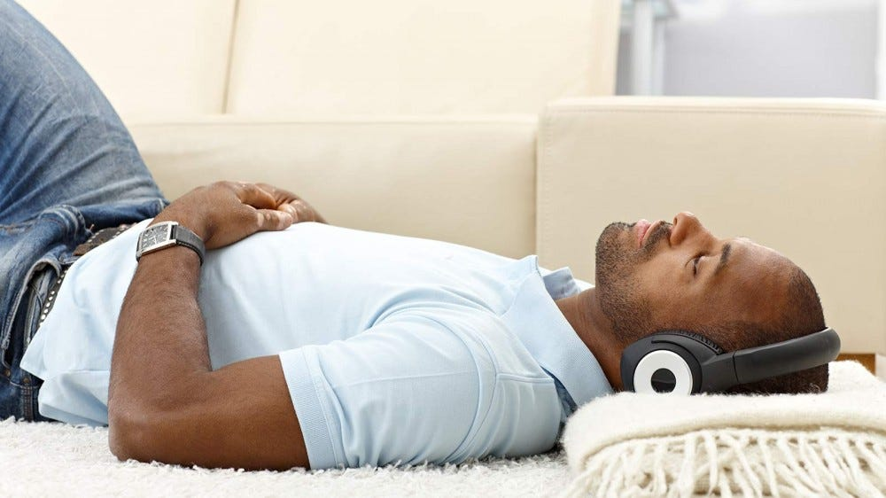 A man lying on a blanket on the floor with noise-canceling headphones on.