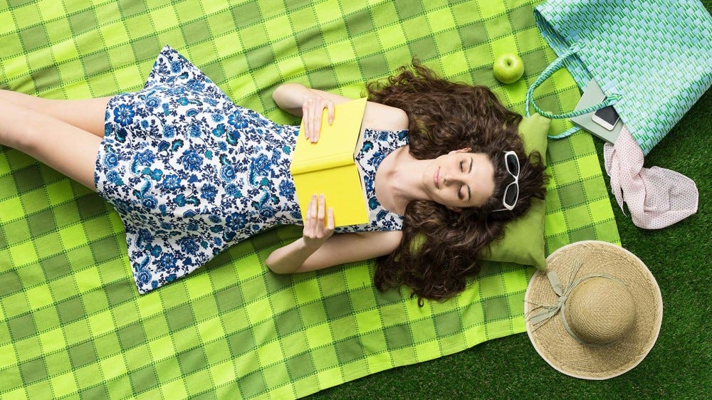 A woman laying on a bright green blanket, reading a book outside.