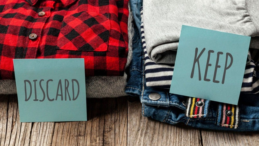 """A stack of clothes labeled """"Discard"""" and another labeled """"Keep."""""""