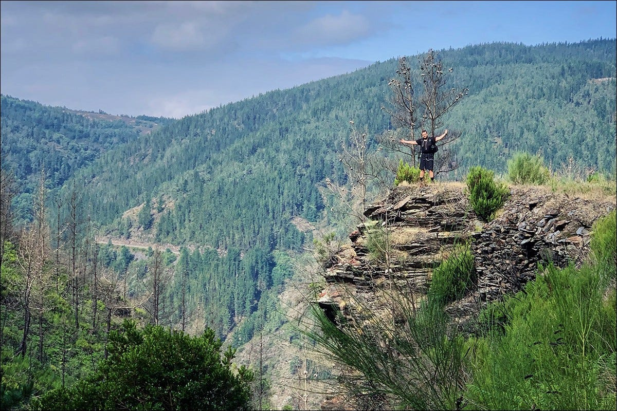 The author standing on a cliff in the mountains.