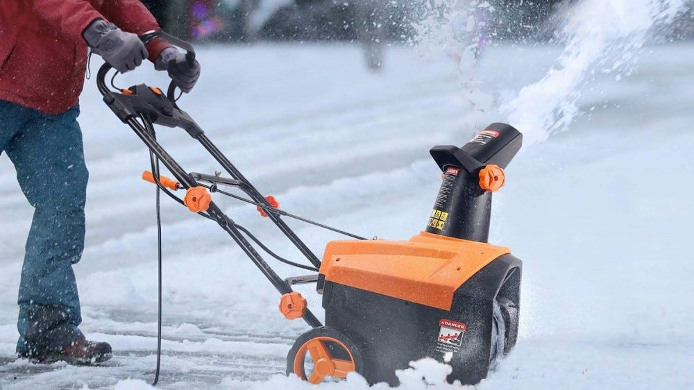 A person plowing the driveway with a snow thrower.