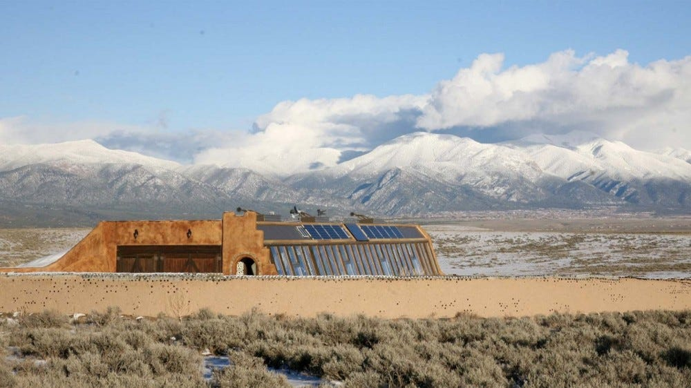 A Earthship sitting in the desert, against a stunning backdrop of mountains and clouds.