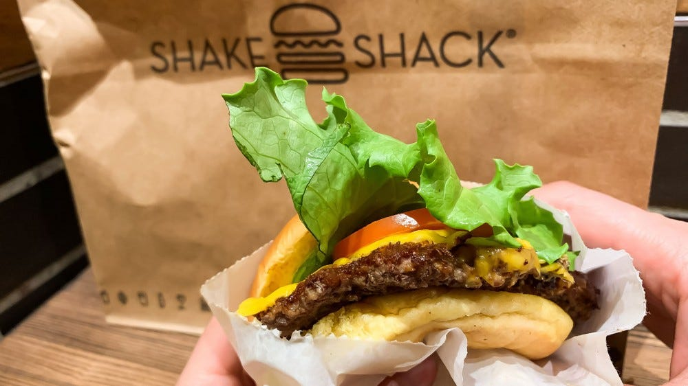 A person holding a Shake Shack burger in front of a bag with the company's logo on it.