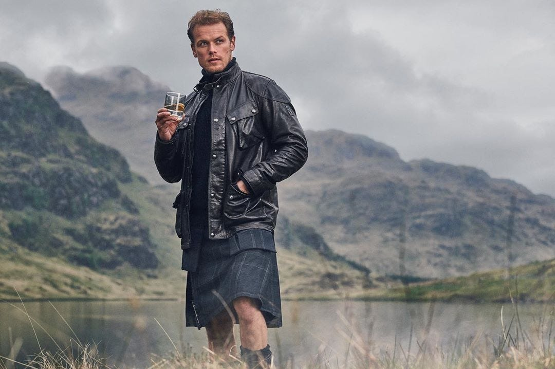 Actor Sam Heughan standing in front of a misty mountain in a kilt, holding a sifter of whiskey.