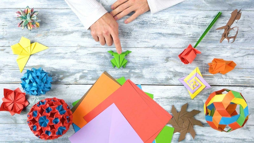 Someone working on various origami creations.