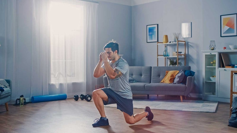 A man doing leg lunges in his living room.
