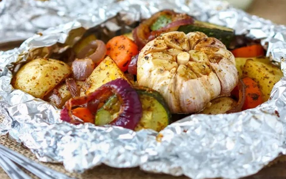 Grilled potatoes, onion, carrots, zucchini, and garlic wrapped in a foil packet (fresh off the grill)