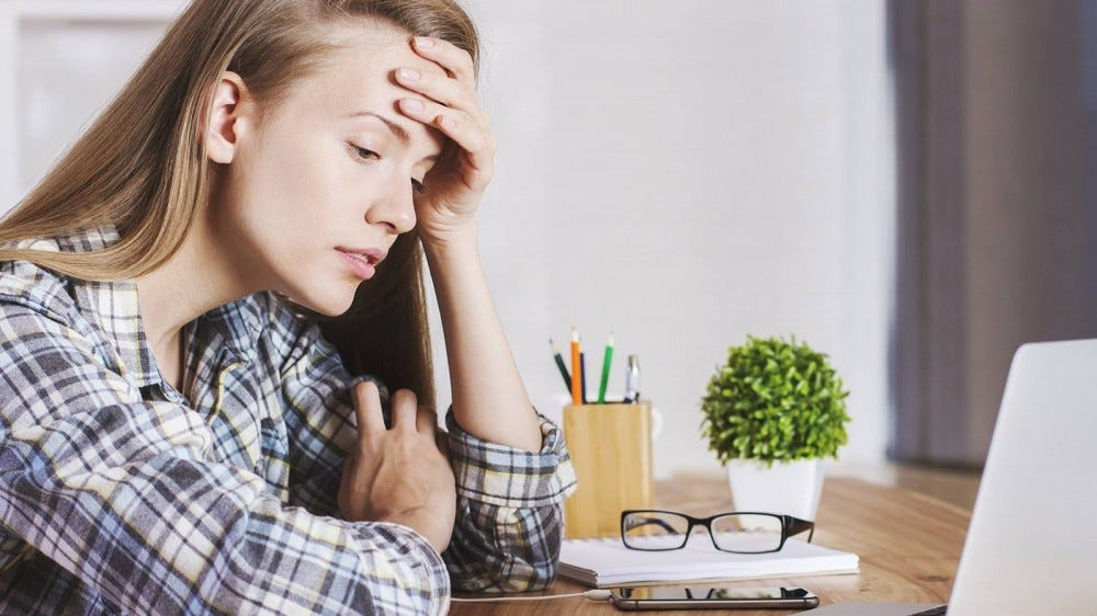 A woman, exhausted, sitting at her desk in the middle of her workday at home.