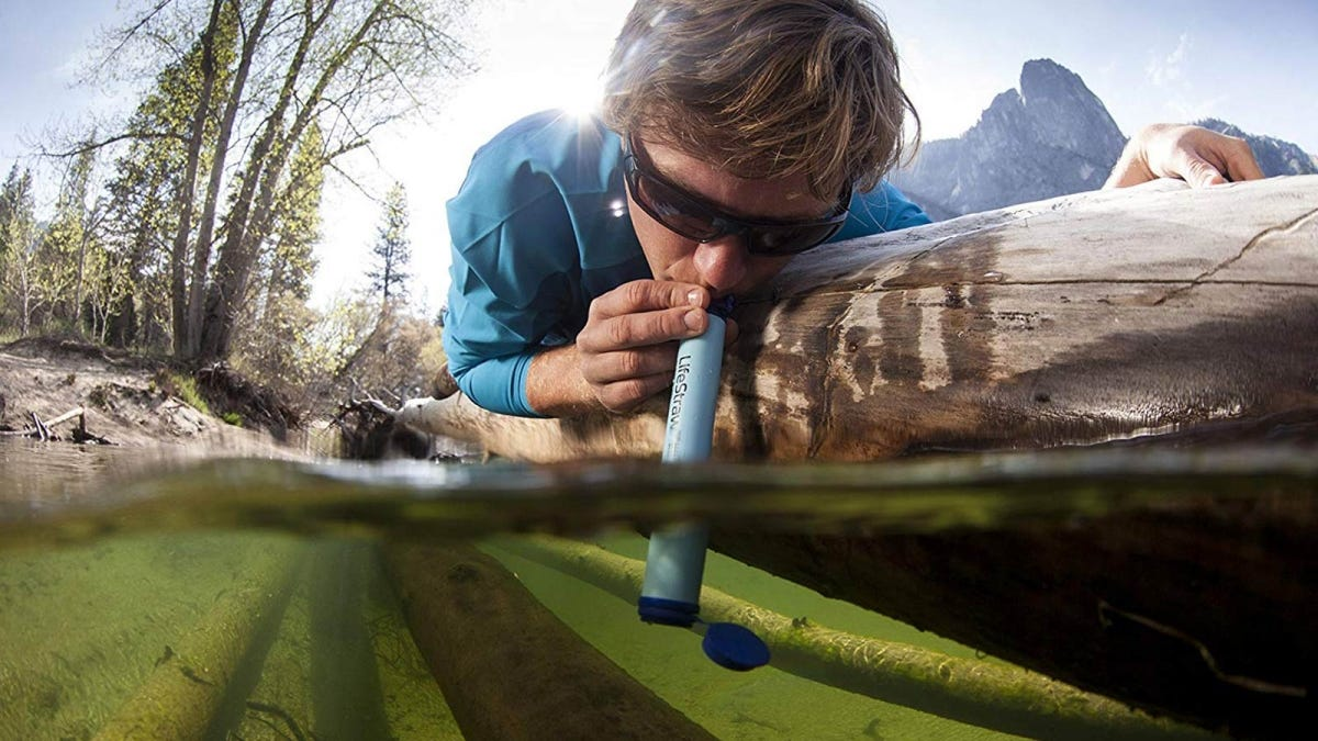 Man drinking directly from a river using the LifeStraw water filter.