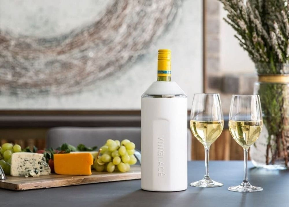 A Vinglace wine chiller sitting on a table with fruit and wine.