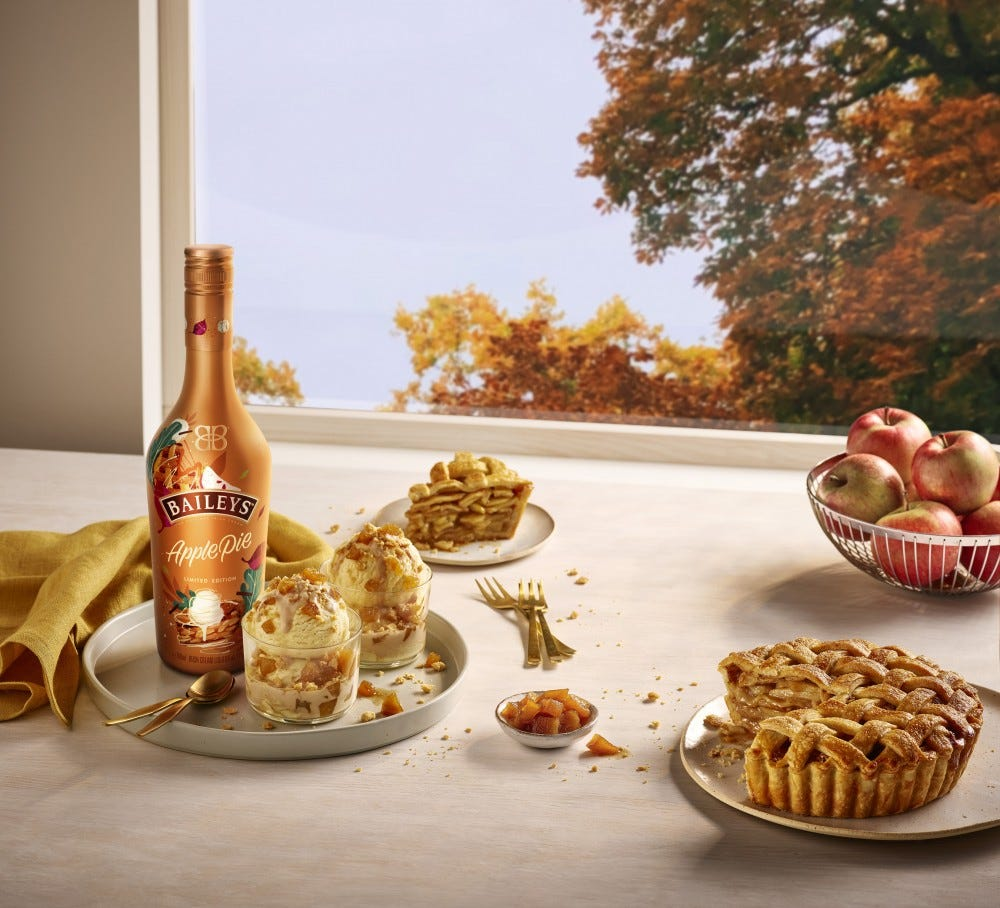 A bottle of Baileys Apple Pie on a windowsill surrounded by apple pie and a bowl of apples.
