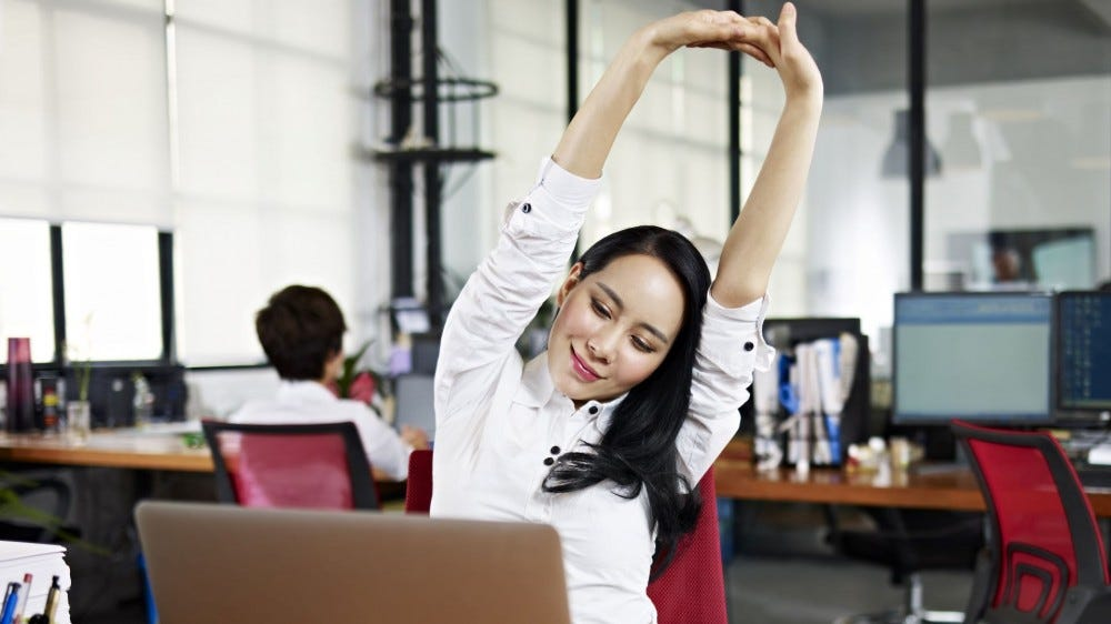 A woman stretching at her desk in an office.