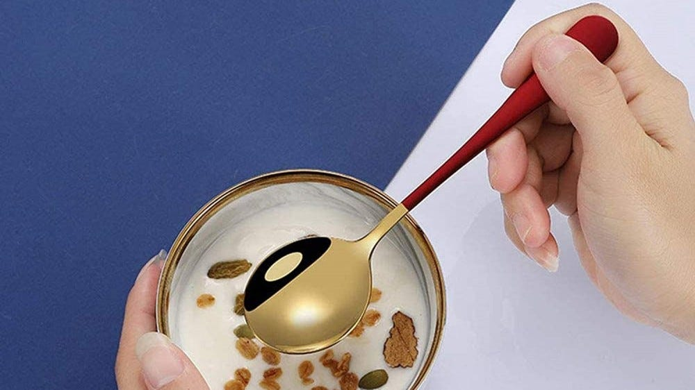 Someone using a gold-colored soup spoon to eat cereal.
