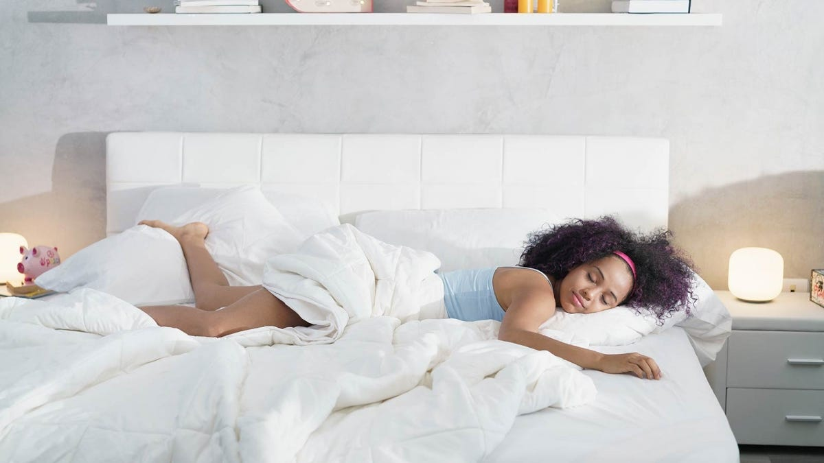 Woman sleeping in on the weekends long after the sun is up and the lights are on.