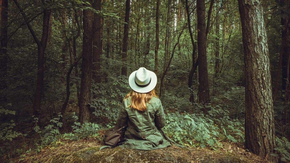 Woman sitting in the woods, taking in the scenery and relaxing.