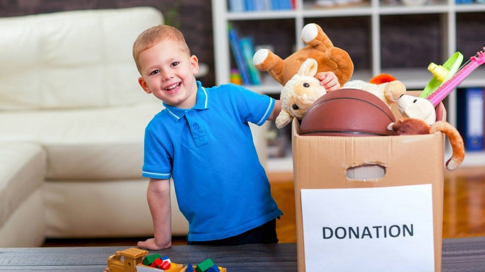 "A little boy standing next to a cardboard box filled with toys and labeled ""Donation."""