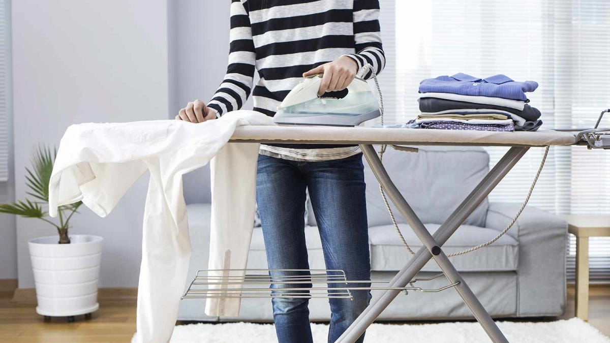 a woman ironing clothes in a sunny living room