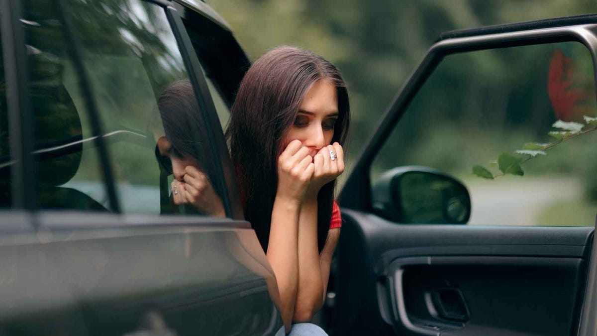A woman leans out the open door of a parked car, hands over her mouth.