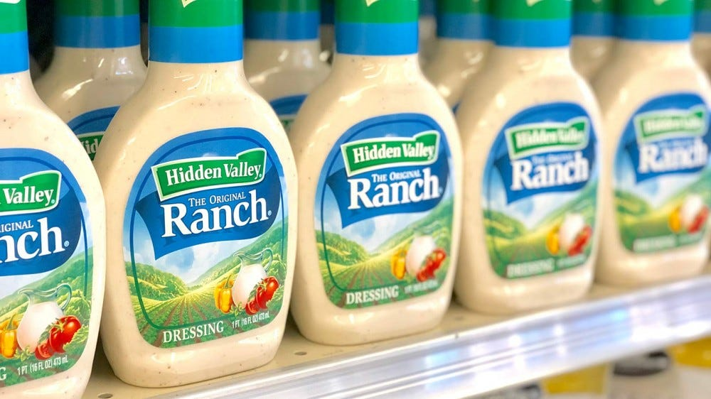 A supermarket shelf stocked with bottles of Hidden Valley Ranch dressing.