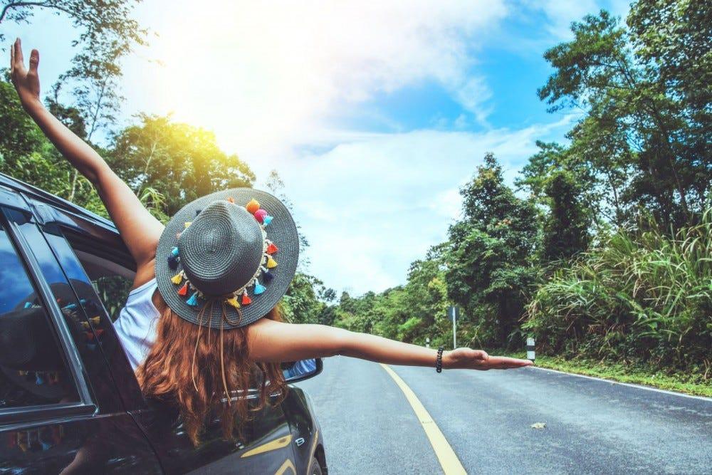 Fiatal lány lóg ki egy autó ablakán, egy napsütéses napon.