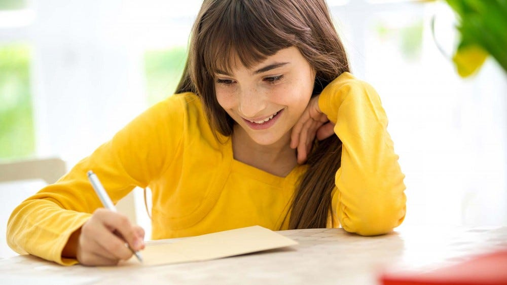 A young girl writing a letter to her grandparents for Grandparents Day.