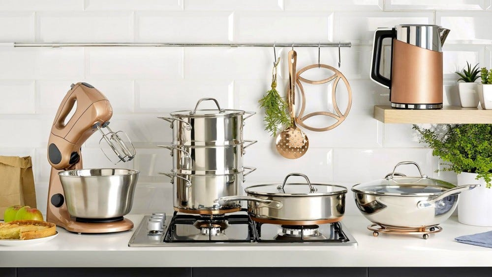 A stand mixer, various pots and pans, and a pitcher on a counter and stovetop.