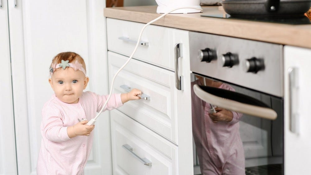 A baby girl playing with an electrical cord in a kitchen.
