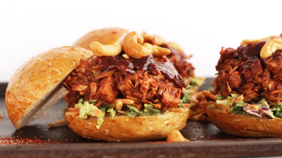 Three bbq jackfruit sandwiches with avocado slaw and cashews all stuffed in multigrain buns.