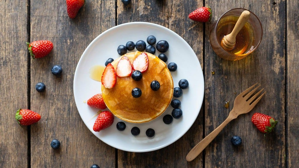 Pancakes topped with fresh fruit next to a dish of honey.